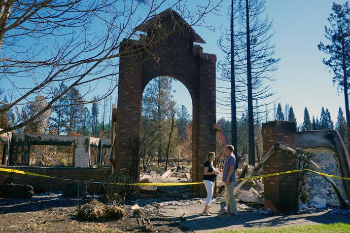 The Rev. Blake Busick and his wife, Peggy, stand in front of their Santa Rosa home after it was destroyed by the California wildfires that started on Oct. 9. Photo by Sue Larson, courtesy of the Rev. Blake Busick.