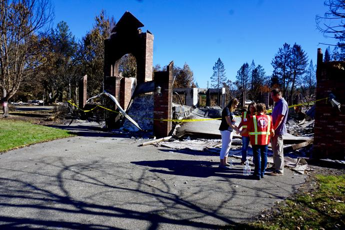 Peggy Busick (left), and her husband, the Rev. Blake Busick (far right), pray with the Rev. Katherine Shoen (second from left), associate pastor, Redwood Covenant Church, and Diana Tollerud, Salvation Army staff, who were in the Santa Rosa, California, neighborhood providing support and care to those affected by wildfires. Photo by Sue Larson, courtesy of the Rev. Blake Busick.