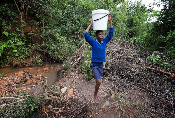 Emelly Maringire, 14, fetches water at the end of her school day. The job of fetching water falls mostly to women and girls. Photo by Mike DuBose, UMNS.