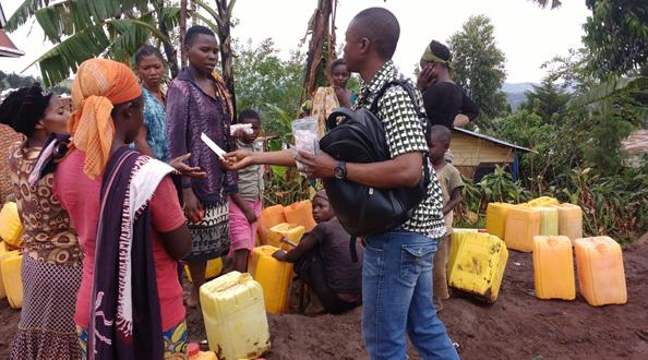 United Methodist volunteers distribute water purification tablets at a watering point in Kavumu, Democratic Republic of Congo. Unsafe drinking water has led to a cholera epidemic in the South Kivu Province. Photo by Philippe Kituka Lolonga, UMNS.