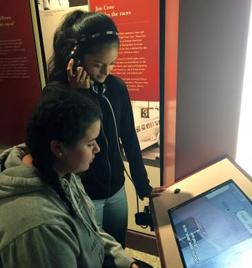 Janel Sarabia (seated) and Aili Martinez take in an exhibit at the Central High School National Historic Site in Little Rock, Ark. They were part of a group of Hispanic youth from Dallas who toured civil rights sites March 11-14, thanks to a grant from the United Methodist Church's National Plan for Hispanic/Latino Ministry. Photo by Amy Spaur.