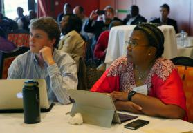 G. Miller Wilbourn, left, of Arkansas, and Benedita Penicela Nhambiu of Mozambique, listen to a presentation at the Connectional Table meeting in Oslo, Norway. Nhambiu leads the Connectional Table's working group on the denomination's worldwide nature. Photo by Heather Hahn, UMNS.