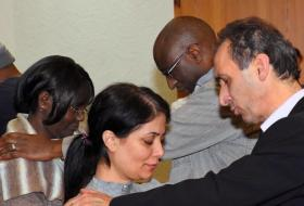 During a seminar on migrant leadership in Germany presented by the General Board of Global Ministries, people from many cultures pray for each other. Photo courtesy of Global Ministries.