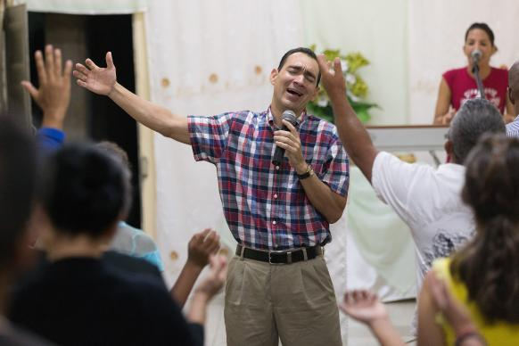 The Rev. Leandro Cordero leads a song at A Place of Hope Methodist Church in Santa Clara, Cuba. He is accompanied on the keyboard by his wife, Yenisel Ramos. Photo by Mike DuBose, UMNS.