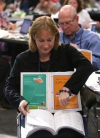 The Rev. Jean Hawxhurst, delegate from the Kentucky Conference, follows the afternoon session of calendar items and petitions at the 2016 United Methodist General Conference in Portland, Ore. The Commission on the General Conference is looking at making this kind of cross-referencing much easier with a digital Daily Christian Advocate. Photo by Kathleen Barry, UMNS.
