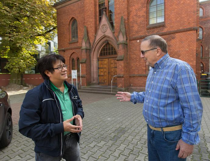 The Revs. Chi My Nguyen (left) and George Miller visit outside the United Methodist Church-Frankfurt City. Nguyen is the only Vietnamese United Methodist pastor in Germany. Miller is coordinator for International and Migrant Ministries for the United Methodist Board of Global Ministries. Photo by Mike DuBose, UMNS.