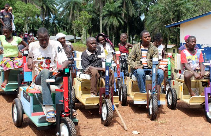 Recipients of Personal Energy Transportation vehicles pose with their new modes of transportation. The United Methodist Women in Liberia distributed the wheelchairs. Photo by Julu Swen, UMNS.