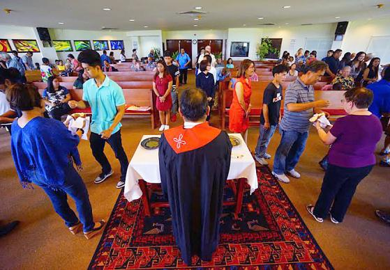 Members of Guam United Methodist Church partake in communion on Pentecost Sunday, June 4. Guam is a U.S. territory in the Pacific that has been threatened with a nuclear missile strike by the leader of North Korea, Kim Jong Un. The Rev. Johann M. Osias, senior pastor, said a similar threat was made in 2013. Photo courtesy of Hiro Kurashina.