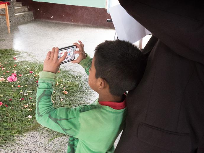 A young member of Iglesia Nacional Methodista Primitiva Fuente De Vida, joins in as one of the photographers during a visit from U.S. United Methodist bishops and church leaders.