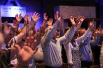 At a speaker's request, members of the Wesleyan Covenant Association raised hands in prayer during the group's Oct. 14 gathering at The Woodlands United Methodist Church, near Houston. Photo by Shannon Martin.