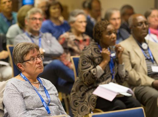 Participants, some using translation equipment, listen to a presentation at the International Health Forum of The United Methodist Church in Stuttgart, Germany. Photo by Mike DuBose, UMNS.