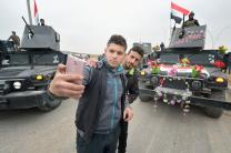 Two residents of Mosul celebrate the partial liberation of their city from control by the Islamic State group by taking a selfie in front of festooned army vehicles. Although a portion of the city has been liberated from ISIS, fierce fighting is predicted as the army moves to retake the remainder of the city. Photo © Paul Jeffrey.