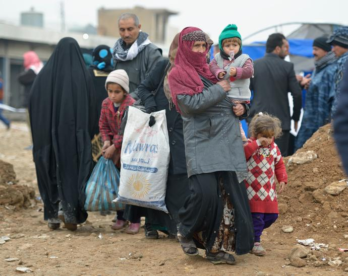 Displaced by fighting between the Iraqi army and the Islamic State group, a family leaves a processing center for displaced families outside Mosul, Iraq. Although the eastern portion of the city has been liberated from ISIS, fierce fighting is predicted as the army moves to retake the remainder of the city. Photo © Paul Jeffrey.