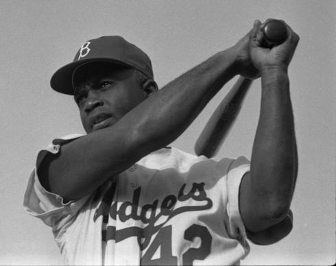 Baseball great Jackie Robinson swings a bat in his Dodgers uniform, dated 1954. This is a photo taken by staff photographer Bob Sandberg of LOOK Magazine, and is part of the LOOK Magazine Photograph Collection at the Library of Congress. Courtesy of Wikimedia Commons.