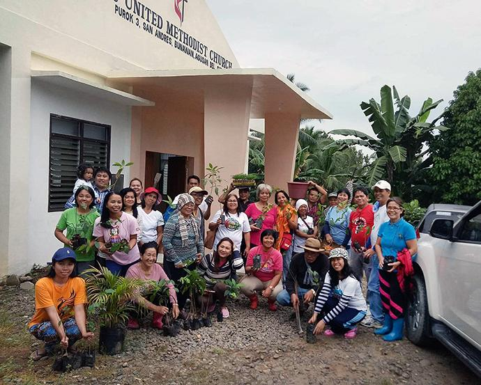 The Rev. Janeth Rufino (kneeling, fourth from left) pauses for a group photo before heading to a farm to plant fruit-bearing trees. More than 500 clergy and laity members from across the Davao area of the Philippines joined the endeavor. Photo courtesy of the Rev. Janeth Rufino.