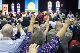Attendees of the Kentucky Annual Conference raise their arms in prayer in the morning