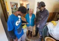 The Rev. Susan Ferguson (center) of Asbury United Methodist Church in Lafayette, La., prays with Trent Noel (right) and his son, Jay Barnes, who are gutting flood-damaged drywall at the home of Noel's mother in Lafayette, La., in August 2016. As the one-year anniversary of the flood approaches, United Methodists in Louisiana are looking for more volunteer teams to continue the recovery work. File photo by Mike DuBose, UMNS.