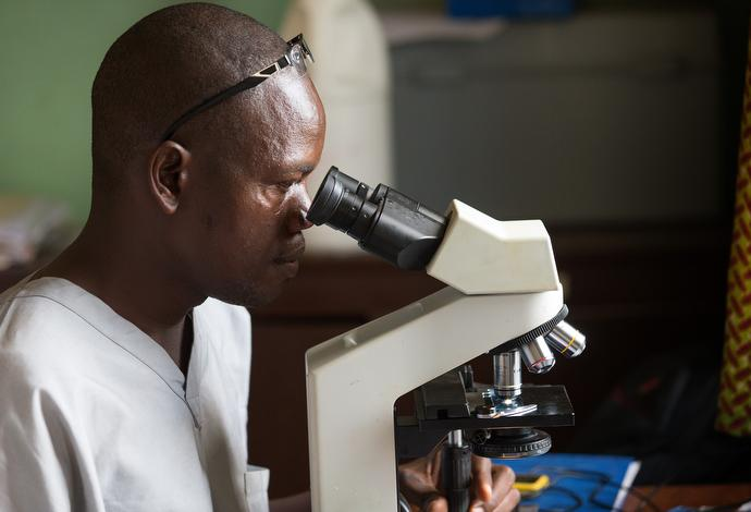 Andrew Brimah reads a microscope slide for tuberculosis at the Ganta Leprosy and TB Rehab Center. Photo by Mike DuBose, UMNS.
