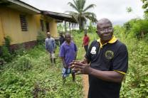 The Rev. Joseph Theoway (front) describes his vision for the restoration of the Liberian Annual Conference's agricultural center in White Plains, which was destroyed during the country's civil war. Theoway is flanked by caretakers who are maintaining what is left of the facility.