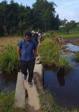 Dr. Shane Sam Mathew (front) leads a visit to a farm near Ganta United Methodist Hospital in Liberia. The 25-year-old dentist was killed in a fire at his residence. Photo courtesy of Ganta United Methodist Hospital.