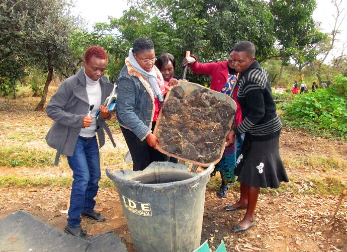 Women work with manure to create green fertilizer during a training workshop in Harare, Zimbabwe. Photo by Kudzai Chingwe, UMNS.