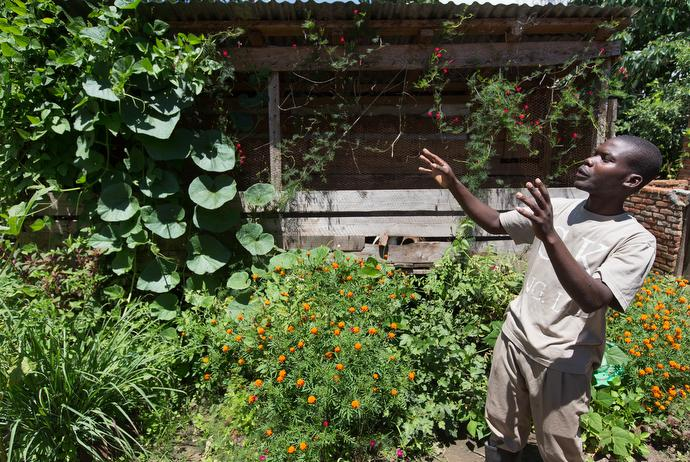Joseph Kaipa shows off the integrated farming techniques in use at the United Methodist farm in Madisi, Malawi. Climbing plants are trained to grow on the sides of a rabbit hutch. Photo by Mike DuBose, UMNS.
