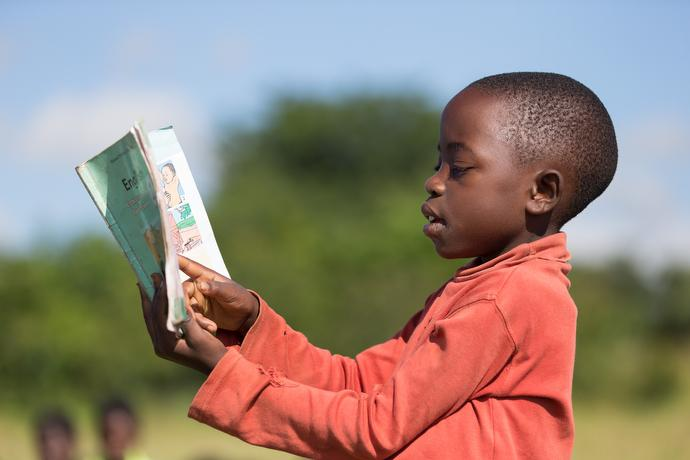 Mary John reads from an English textbook at Liuto Primary School near Madisi, Malawi. Photo by Mike DuBose, UMNS.