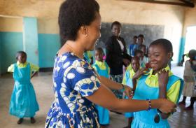 Mercy Chikhosi helps Beth Jesara try on her new school uniform at Liuto Primary School near Madisi, Malawi. The uniforms were bought with donations from several United Methodist churches in Middle Tennessee. Photo by Mike DuBose, UMNS.