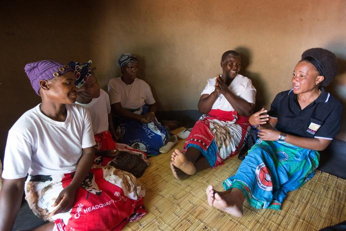 Mercy Chikhosi (right) visits with  women leaders in the home villagers constructed for her in Nkhafi, Malawi. Chikhosi, a graduate of United Methodist Africa University, served as the first health coordinator for the Malawi United Methodist Church. Photo by Mike DuBose, UMNS.