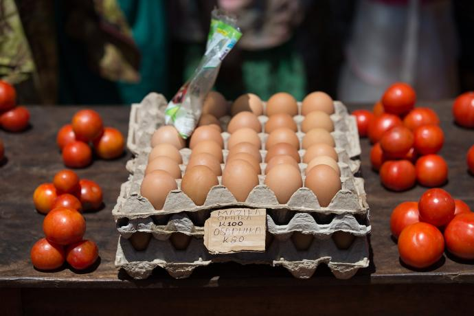 Tomatoes and eggs are offered for sale at a roadside stand started with United Methodist micro-financing in Khosi, Malawi. The sign says boiled eggs cost 100 kwacha (about 14 U.S. cents) and raw eggs are 80 kwacha (about 11 cents). Photo by Mike DuBose, UMNS.
