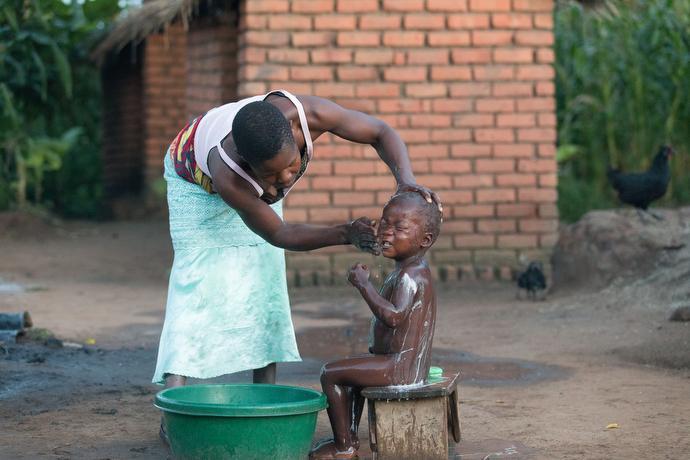 Violet Chandawira bathes her son Demphero Muaza in Mzira, Malawi. Photo by Mike DuBose, UMNS.