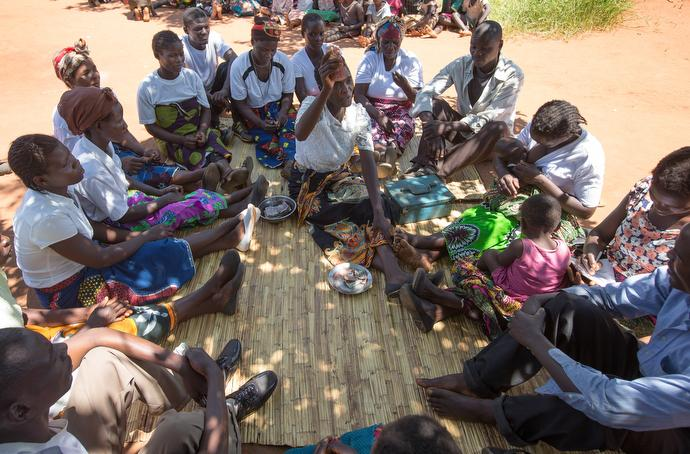 The Tilimbike cooperative banking group meets weekly on a bamboo mat under a shade tree in Khosi, Malawi. Using United Methodist startup money, the group is now self-sustaining with members contributing weekly and giving small loans to start new business ventures. Photo by Mike DuBose, UMNS.