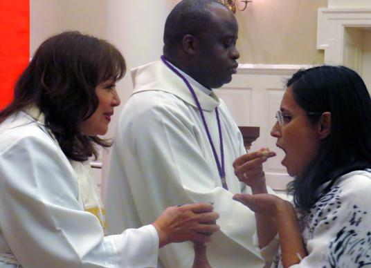 Bishop Minerva Carcaño and Bishop Mande Muyombo offer communion during opening worship at the 46th MARCHA Assembly in Dallas. MARCHA, the denomination's Hispanic/Latino caucus, met at a Dallas hotel but held worship services in Perkins Chapel, at Southern Methodist University's Perkins School of Theology. Photo by Sam Hodges, UMNS.