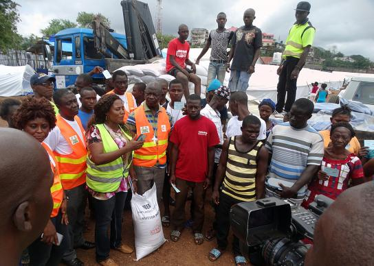 At Juba Camp in Freetown, Sierra Leone, Bishop John Yambasu (fourth from left, front row) leads a symbolic handing over of 200 bags of rice to the Office of National Security, the government agency in charge of coordinating welfare matters for survivors of deadly mudslide Aug. 14. Because survivors are not allowed to cook in their temporary plastic-cover homes, the ONS hires people to prepare food for them three times a day. Photo by Phileas Jusu, UMNS.
