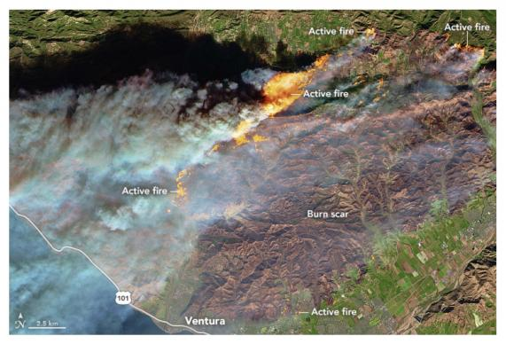 A NASA satellite image shows active fires affecting a forested, hilly area north of Ventura, with flames encroaching into the northern edge of the city. On Dec. 6, 2017, Cal Fire estimated that at least 12,000 structures were threatened by fire.