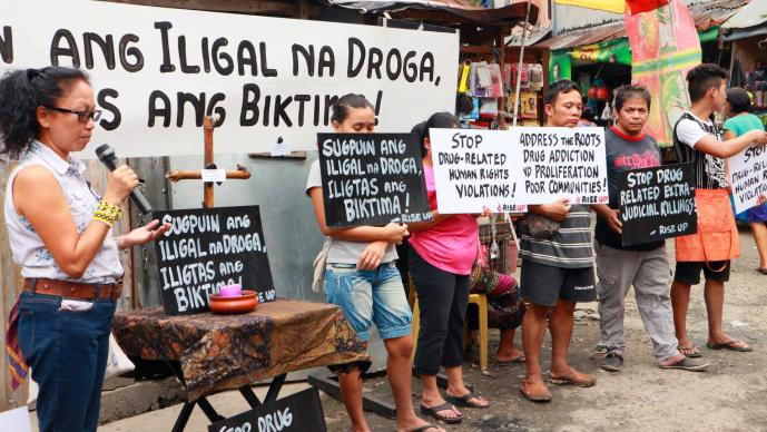 In a file photo from December 2016, Norma Dollaga, on left with microphone, speaks during an ecumenical action of Kadamay: Stop the Killings, a community organization that advocates for the poor in urban communities, in Quezon City, Philippines. The placards in Filipino say,