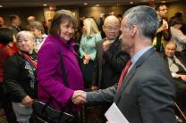 Bishop Karen Oliveto (left) and the Rev. Walter Fenton (right) shake hands during the April 25 oral hearing before the United Methodist Judicial Council meeting in Newark, N.J. Fenton is the analyst for Good News, which advocates that the church hold the line on homosexuality teachings. Photo by Mike DuBose, UMNS