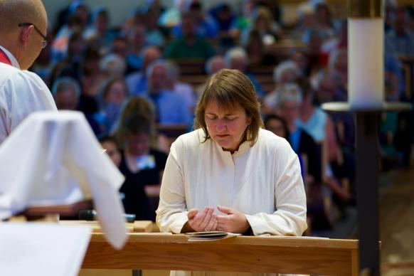 Bishop Karen Oliveto, the first openly gay bishop in The United Methodist Church, kneels during the consecration service held on July 16, 2016, at Paradise Valley United Methodist Church in Scottsdale, Arizona. Photo by Patrick Scriven