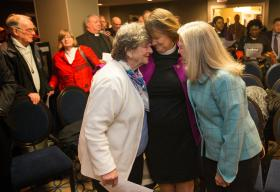 Bishop Karen Oliveto (center, standing) shares a moment with her mother, Nelle Oliveto (left) and her wife, Robin Ridenour, after a hearing before the United Methodist Judicial Council meeting in Newark, N.J. The denomination's top court heard arguments on a petition questioning whether a gay pastor can serve as a bishop in The United Methodist Church. Any decision on that petition could affect Oliveto, the denomination's first openly gay bishop. Photo by Mike DuBose, UMNS.