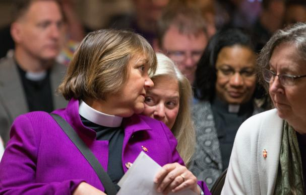 Bishop Karen Oliveto (left) leans over to speak with her wife, Robin Ridenour (behind Oliveto) prior to a meeting of the United Methodist Judicial Council in Newark, N.J. The denomination's top court ruled on April 28 that the consecration of a gay bishop violates church law. At right is Bishop Elaine Stanovsky. Photo by Mike DuBose, UMNS