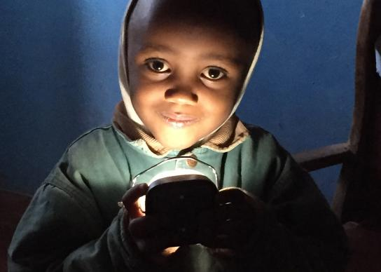 A young boy holds a d.light solar lamp at his home in the Mathare slum, Nairobi, Kenya. Wespath Benefits and Investments has invested about $30 million in solar projects, including d.light. Photo courtesy of d.light