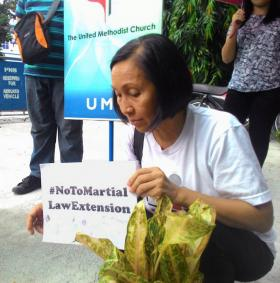 Phebe G. Crismo, executive secretary of the Board of Christian Education and Discipleship for the Philippines conference, holds a sign with the hashtag #NoToMartialLawExtension during a candle-lighting gathering in front of The United Methodist Church Headquarters in Manila. A 60-day martial rule proclamation for Mindanao expired on July 22, but the Filipino Congress voted to extend it through the end of the year. Photo by Liza Cortez.