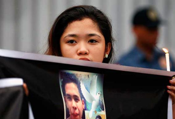 Aminah A. Lucena, a United Methodist youth, holds a photo of Kian delos Santos during a candle-lighting protest in front of the Philippine National Police headquarters in Quezon City on Aug. 23. Kian, a 17-year-old student, was a victim of extrajudicial killings under the Operation Galugad of the War on Drugs campaign of President Rodrigo Duterte. Photo by Miguel de Guzman, courtesy of The Philippine Star.