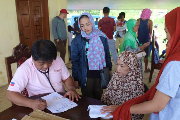 Dr. Emilio S. Caoagdan (left), a volunteer from Makilala United Methodist Church, sees patients who have fled fighting with Islamic State militants at an evacuation center in Bito-Buadi, Marawi City, Philippines. Photo by the Rev. Israel M Painit