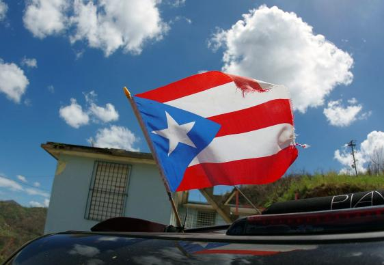 A torn flag of Puerto Rico waves from a car a week after Hurricane Maria ravaged the island. Photo by the Rev. Gustavo Vasquez, UMNS.