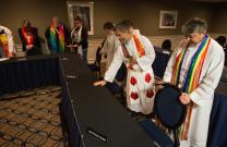 Members of the United Methodist Queer Clergy Caucus and supporters pray over the seating area to be used by the United Methodist Judicial Council during their meeting in Newark, N.J. The denomination's top court held an oral hearing on a petition questioning whether a gay pastor can serve as a bishop in The United Methodist Church. Photo by Mike DuBose, UMNS.