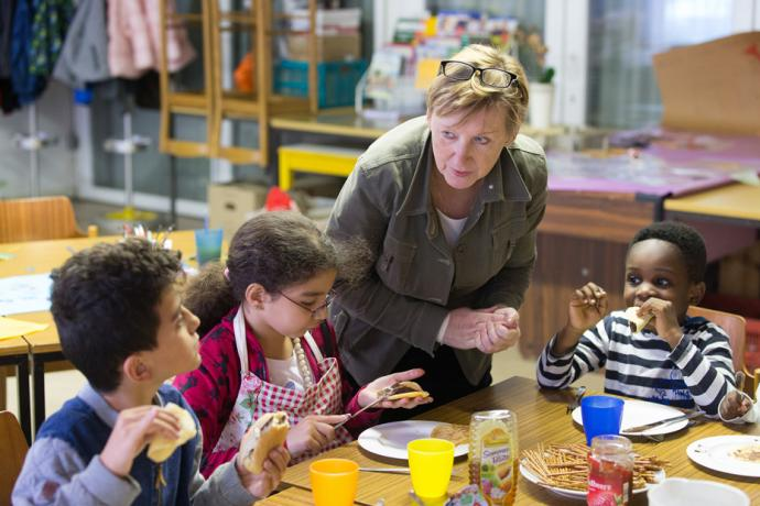 Volunteer Hannah Guzinski helps serve a meal to immigrant children in an educational enrichment program at the United Methodist Peace Church in Hamburg, Germany. Photo by Mike DuBuse, UMNS.