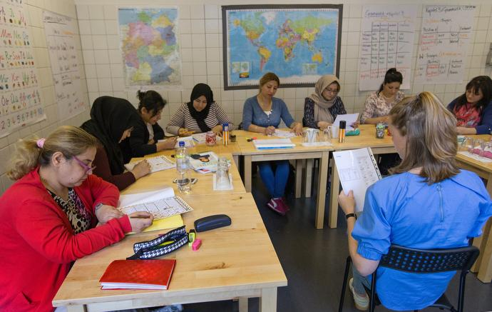 Carolin Hein (right foreground) conducts a German language class for refugees at the United Methodist headquarters in Frankfurt, Germany.