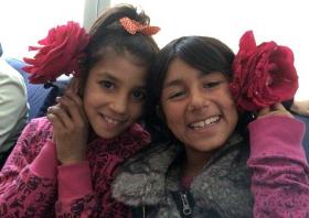 Two Roma children pose with flowers and smile during an excursion in a mini-bus. They are part of a school project sponsored by The United Methodist Church in Macedonia. Photo courtesy of Christina Cekov.