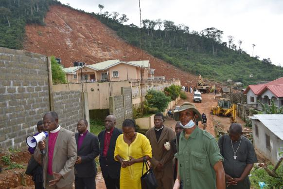United Methodist Bishop John Yambasu (with megaphone) leads community members, relief workers and other clergy in prayer at the site of a massive mudslide that killed hundreds of people near Freetown, Sierra Leone. Photo by Phileas Jusu, UMNS